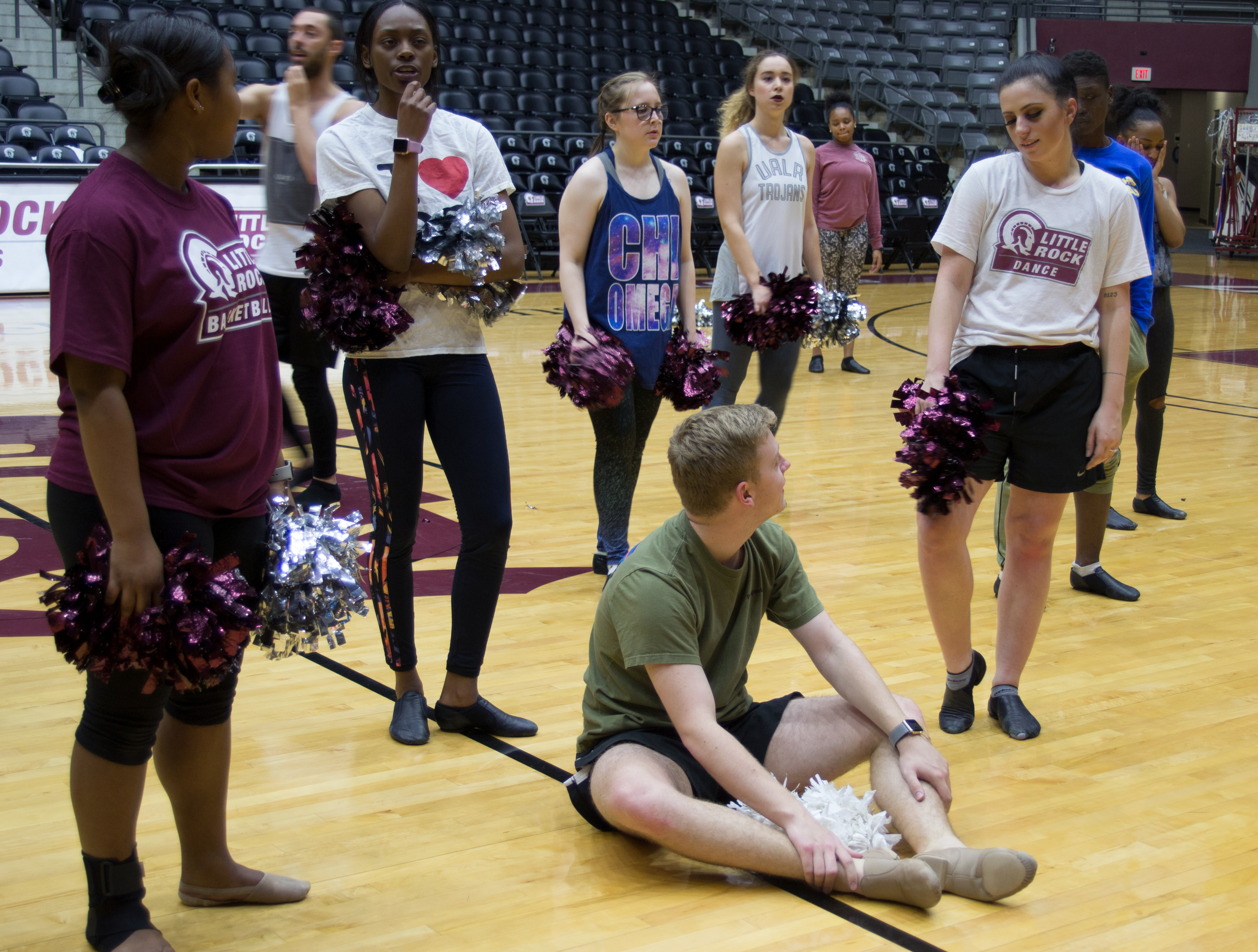 UA Little Rock dance team members gather around for a quick break during practice.